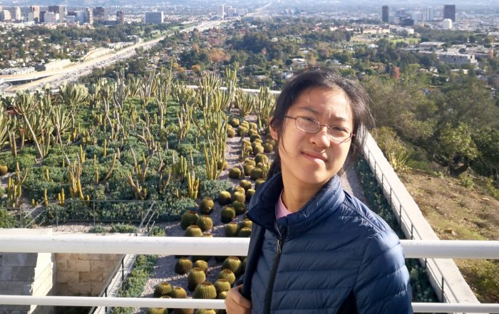 Wendi Zhou smiling, outdoors, a desert city skyline in the background