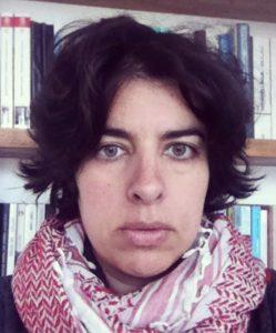 Netalie Braun, wearing scarf in front of bookshelf