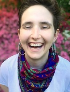 Shelby Handler laughing, wearing scarf and multilayered shirt