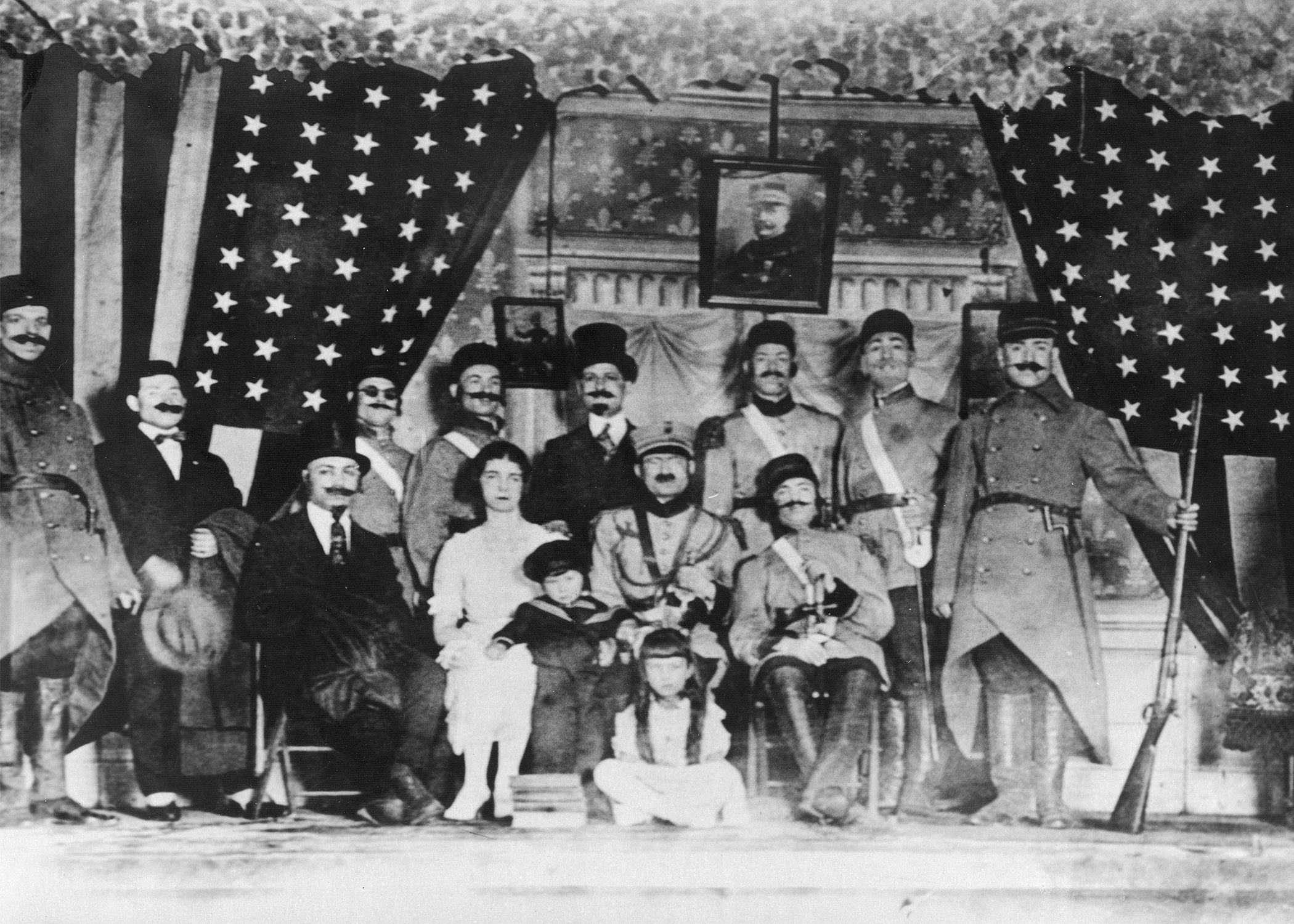 Black and white photo of Sephardic theater troupe; actors dressed in military costume with American flags in background.